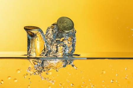 Euro coins with water splash on  yellow background Stock Photo