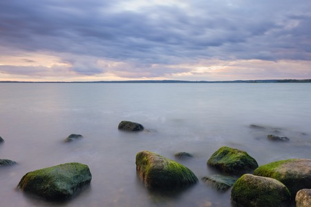long lake: Stones in lake over sunset, long time exposure effect.