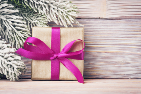 Gift box with pink ribbon over wooden background