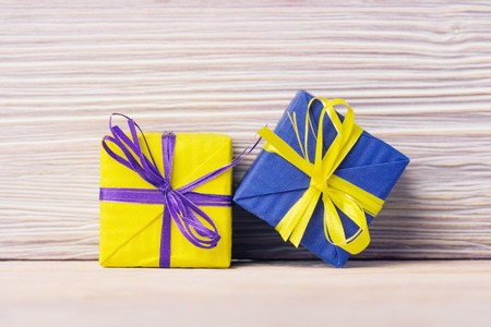 Yellow and blue gift boxes over old wooden background