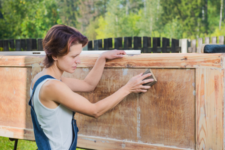 old furniture: Mature woman is polishing old furniture outdoors Stock Photo