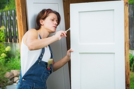 old furniture: Mature woman is painting old furniture outdoors