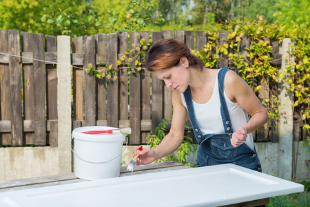 old furniture: Woman renewing old furniture with white paint Stock Photo