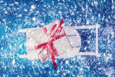 snowbound: Gift box on wooden sled over snowbound background