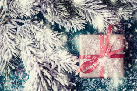 snowbound: Christmas background with gift box and snowbound fir tree Stock Photo
