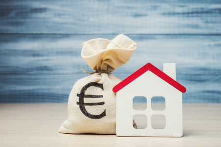 Toy house and money bag with Euro symbol, mortgage concept Stock Photo