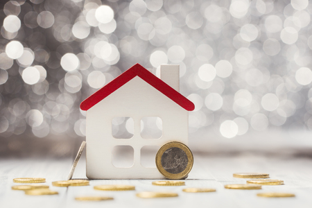 House model and Euro coins over defocused lights