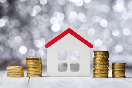 House model and Euro coins over defocused lights, mortgage concept