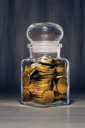 Euro coins in transparent glass container