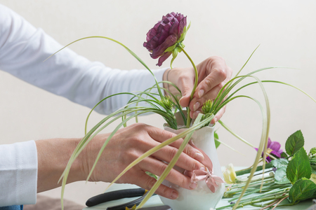 Close up of woman hands making flower decoration