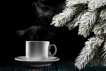 Steaming coffee and Christmas tree branch over black background Stock Photo