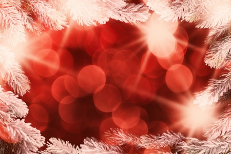 Holiday background with Christmas tree branched frame and defocused lights.
