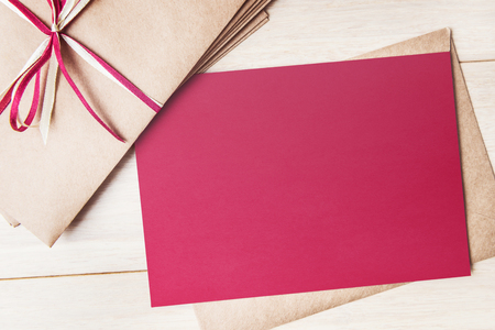 Mock up of red card with envelopes pile on wooden table