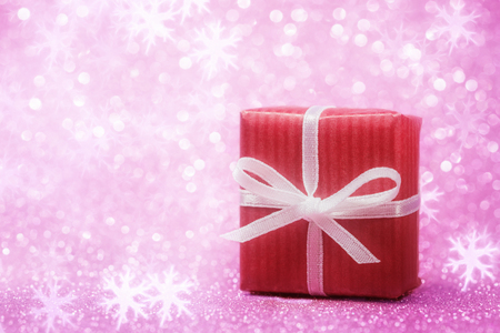 Close up of red gift box over pink holiday background Imagens