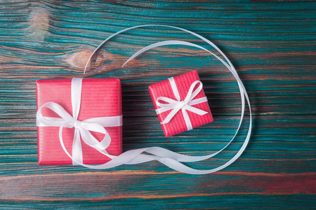 Two red gift boxes over old wooden background