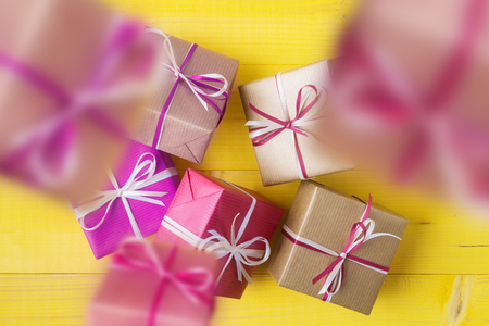 Gift boxes are falling to yellow wooden dackground