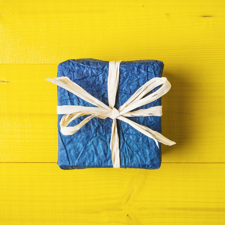 Close up of blue gift box on bright yellow background