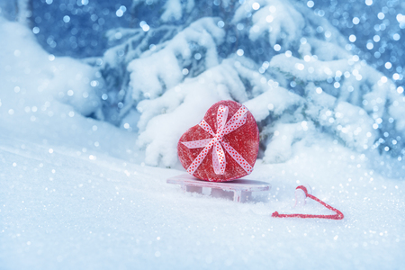 Heart shaped gift box on sleigh in snowy forest. Valentines day 写真素材