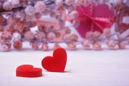 Two bright red hearts over defocused hoarfrost berries and gift box
