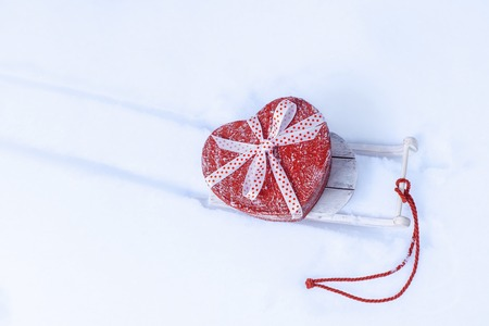 Heart shaped gift box on sleigh in snowy winter forest. Valentines day concept