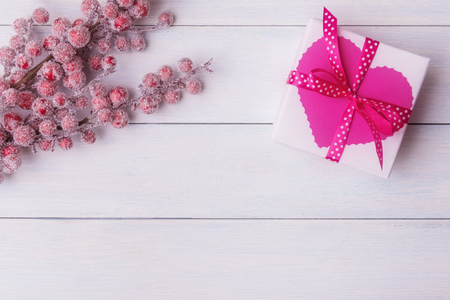 Valentines day concept with pink gift box and hoarfrost berries on white wooden planks