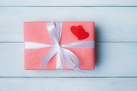 Pink gift box with decorative hearts on blue wooden Banco de Imagens