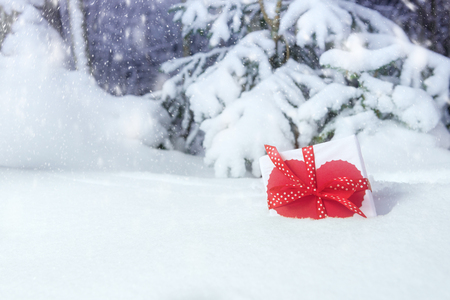 Gift box with decorative heart in snowing winter forest