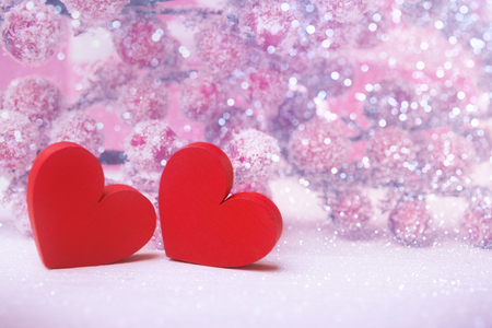Two bright red hearts over defocused hoarfrost berries Banco de Imagens