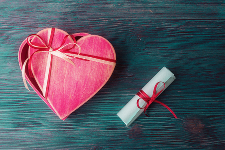 Open hear shaped pink gift box and love letter over blue wooden