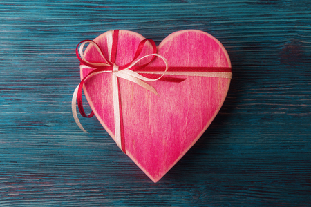 Close up of heart shaped pink gift boxes on blue wooden