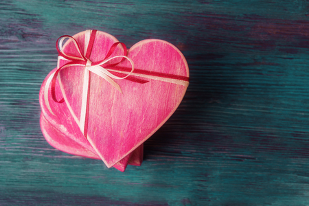 Pile of heart shaped gift boxes on blue wooden
