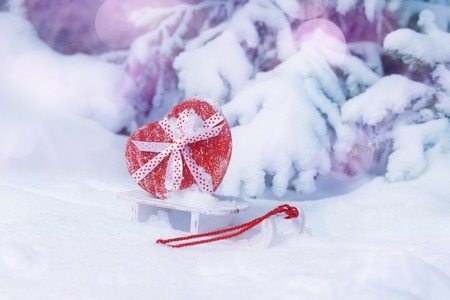 Heart shaped red gift box on sleigh in snowy winter forest. Valentines day concept Banco de Imagens