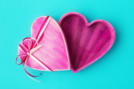 Wooden heart shaped pink gift box on turquoise backdrop.