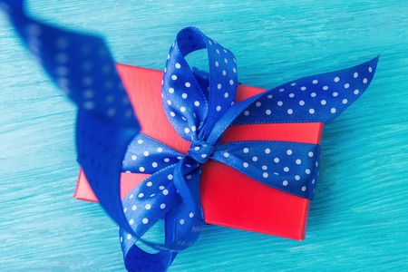 Close up of red gift box with spotted blue bow over wooden Standard-Bild