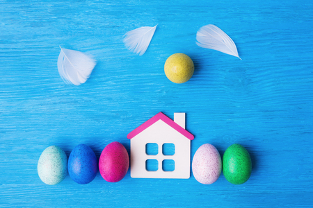 Easter concept with decorative eggs, toy house and feathers as clouds on blue