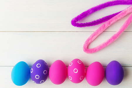 Bunny ears and decorative pink and purple eggs on wooden  with copy space