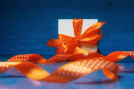 Gift box with spotted orange ribbon on blue