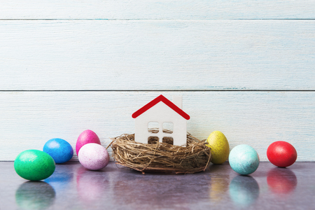 Easter concept with house model in nest and painted eggs 版權商用圖片