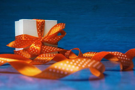 Gift box with spotted orange ribbon against blue 版權商用圖片