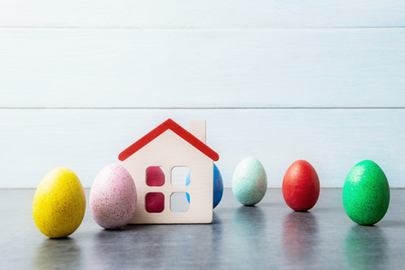 House model with multicolored Easter eggs over light blue wooden