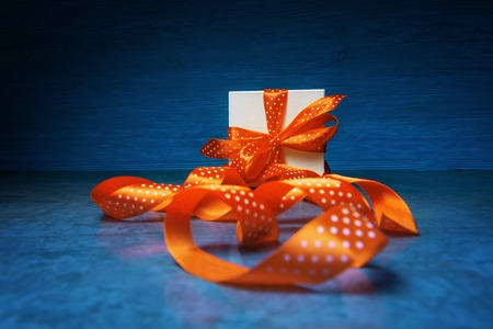 Gift box with spotted orange ribbon over blue