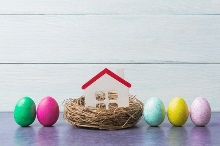 Easter concept with house model in nest and painted eggs on wooden 版權商用圖片