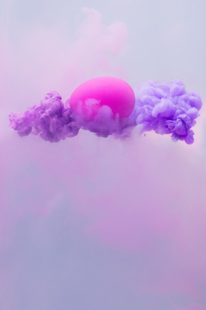 Abstract concept with violet egg in color ink water splash