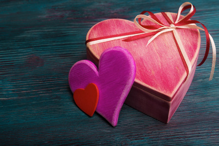 Valentines day concept with heart shaped gift box on rustic wooden background