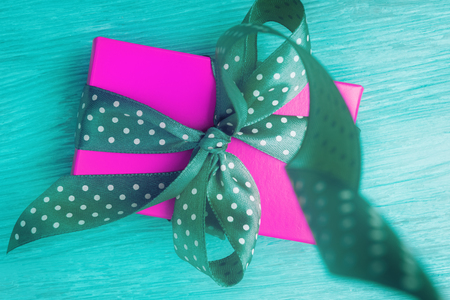 Top view of pink gift box with green ribbon on wooden background Stock fotó