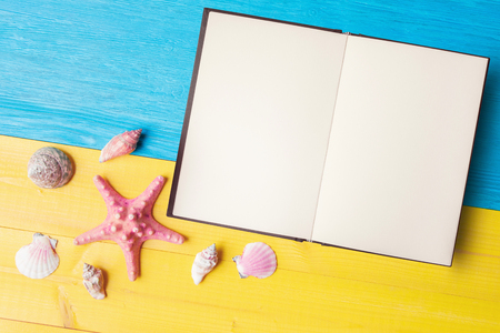 Vacation summer concept with open notebook, seashell and starfish on yellow blue background