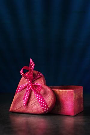 Heart shaped wooden gift box over dark blue background Stock fotó