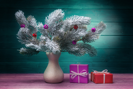 Still life with frosty fir branches and red and pink gift boxes Stock fotó