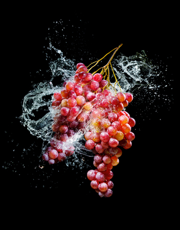 Bunch of grapes in water splash over black background