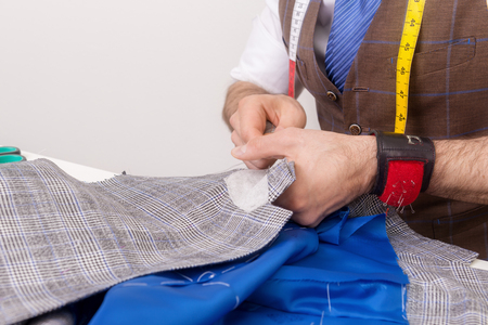 Male tailor hands at working process with fabric